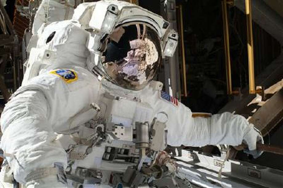 In this Saturday, NASA astronaut Michael Hopkins work to repair an external cooling line on the International Space Station. Photo: AP / NASA