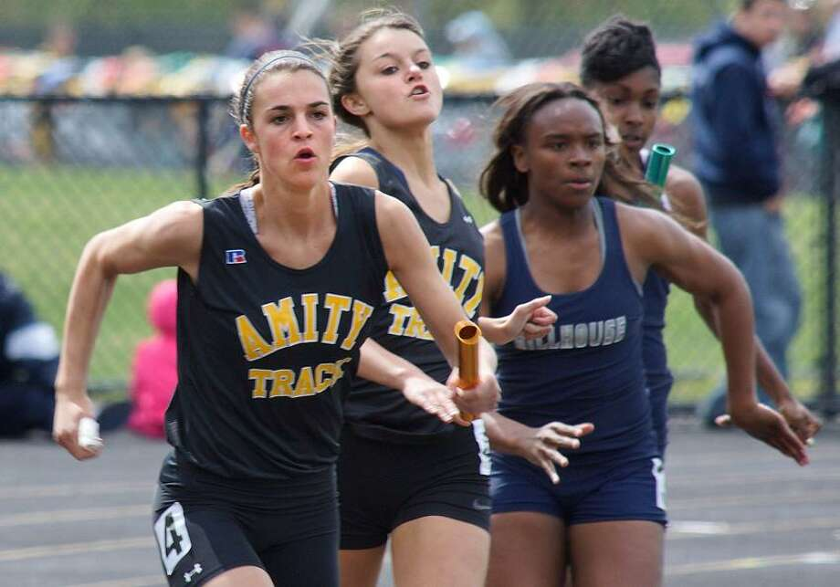 "Amity-- Amity's Allison Maier takes the baton from Shaylyn Sullivan during the 4x100. The Amity girls broke the meet record with this run.  Photo-Peter Casolino/Register <a href=""mailto:pcasolino@newhavenregister.com"">pcasolino@newhavenregister.com</a>"