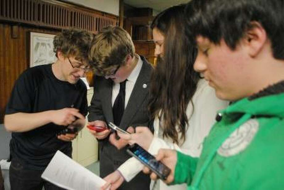 From left to right, Torrington High School students Tomasz Kalinowski, 17, Nick Tomchik, 17, Cassandra Jedlinski, 15, and Chris Beyus, 17 (Oliver Wolcott Tech) use personal electronic devices they hope to make legal in school hallways and the cafeteria. JESSICA GLENZA/Register Citizen.