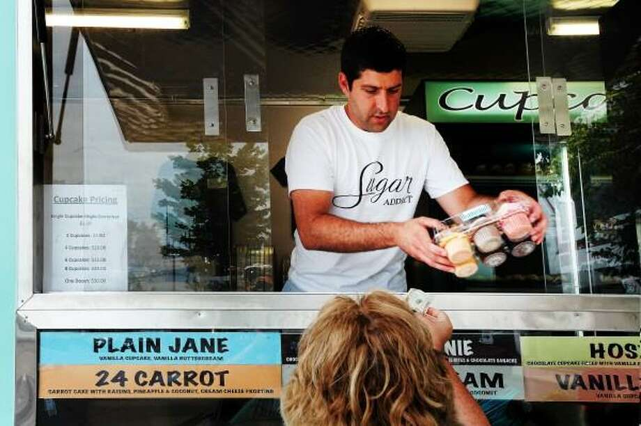 """Vern Williams/New Haven Register Michael DePonte of the """"Sugar"""" cupcake truck serves a selection of the confection to Mary Beth Mills in the 1 Long Wharf parking lot July 3, 2013."""