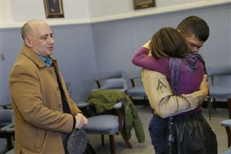 Lance Cpl. Christopher Mohedano-Hernandez, right, is hugged by his sister Kate Mohedano, 12, while his step-father Luis Mohedano looks on after an adoption ceremony in New York. Photo: AP / AP