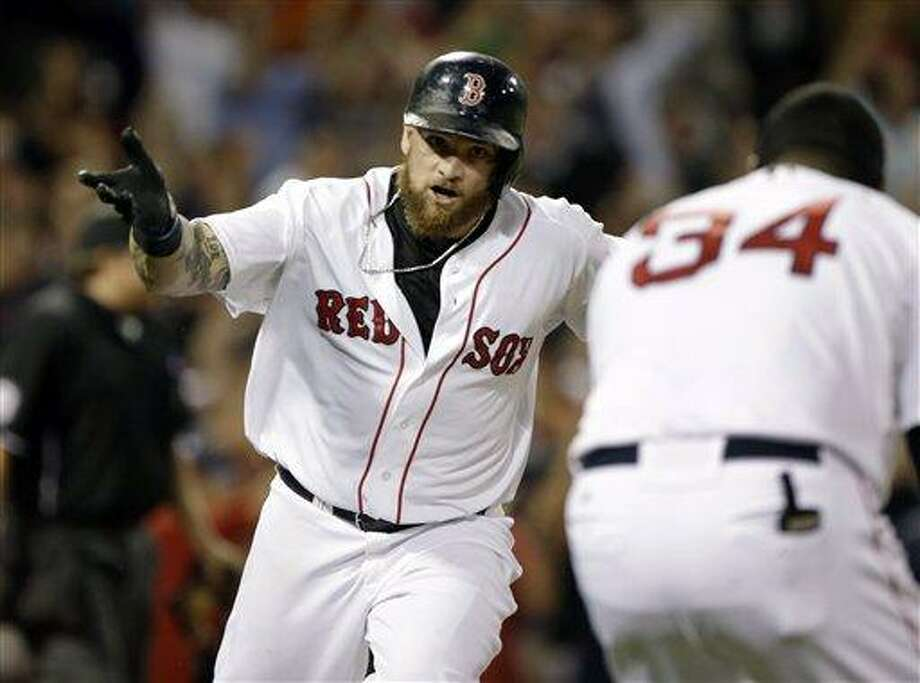 Boston Red Sox's Jonny Gomes runs to first where teammate David Ortiz waits to celebrate his pinch-hit walk-off solo home run in the ninth inning to win an interleague baseball game against the San Diego Padres 2-1 at Fenway Park in Boston, Wednesday, July 3, 2013. (AP Photo/Elise Amendola) Photo: AP / AP