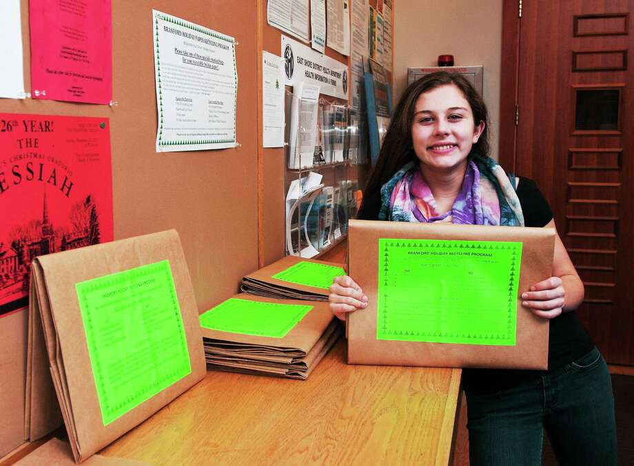 "(Peter Casolino ó New Haven Register)   Etta Hanlon, a Branford High School student, developed ""holiday sacks,"" a recycling bag for wrapping paper that will be pickup up on the curb by the Branford town for recycling. The sacks were distributed in the schools and at town locations like this one at town hall.  pcasolino@NewHavenRegister Photo: Journal Register Co."
