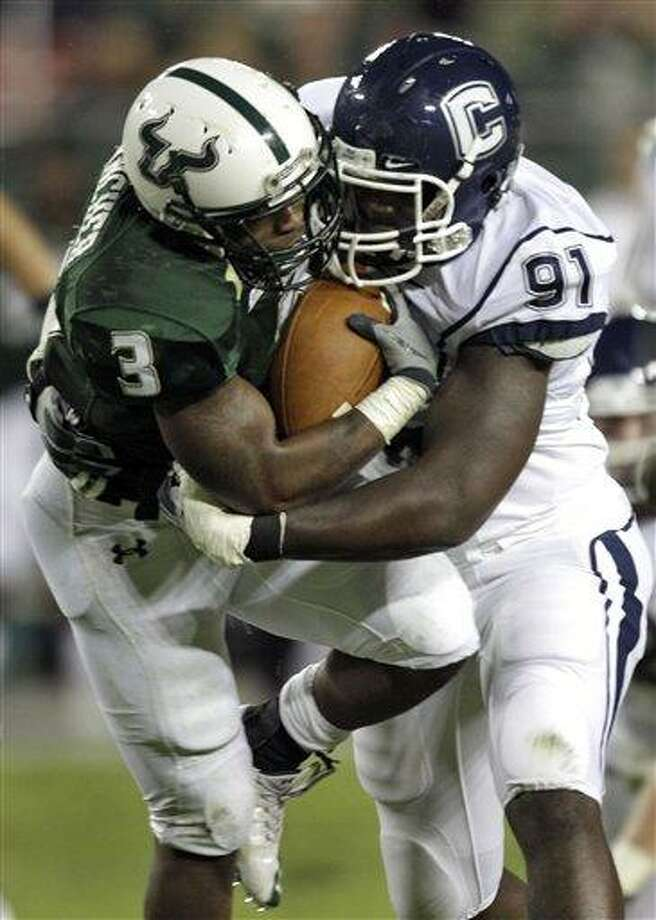 South Florida running back Moise Plancher (3) gets rapped up by Connecticut defensive end Jesse Joseph during a game in 2010. (AP File Photo/Chris O'Meara) Photo: ASSOCIATED PRESS / AP2010