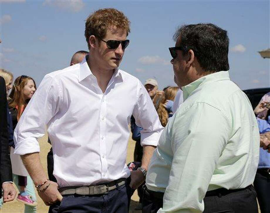 New Jersey Gov. Chris Christie, right, talks to Britain's Prince Harry while visiting the area hit by Superstorm Sandy, Tuesday, May 14, 2013, in Seaside Heights, N.J.  Prince Harry began a tour  of New Jersey's storm-damaged coastline, inspecting dune construction, walking past destroyed homes and shaking hands with police and other emergency workers.  New Jersey sustained about $37 billion worth of damage from the storm. (AP Photo/Mel Evans, Pool) Photo: ASSOCIATED PRESS / AP2013