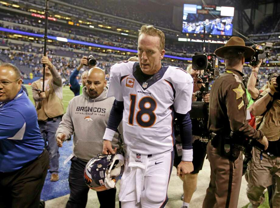 Denver Broncos quarterback Peyton Manning walks off the field after Sunday's game against the Colts in Indianapolis. The Colts won 39-33. Photo: Michael Conroy — The Associated Press   / AP