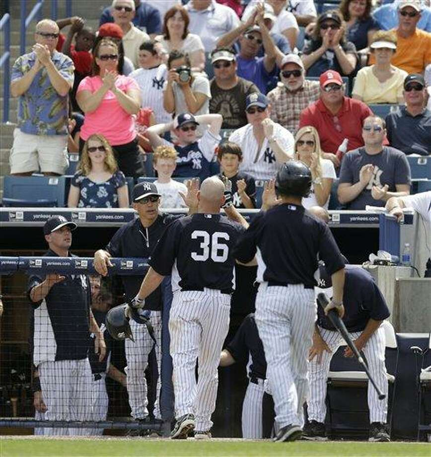 Fans and New York Yankees manager Joe Girardi greet and applaud Yankees Kevin Youkilis (36) after Youkilis hit a solo home run in a spring training baseball game in Tampa, Fla., Monday, March 11, 2013.  (AP Photo/Kathy Willens) Photo: AP / AP