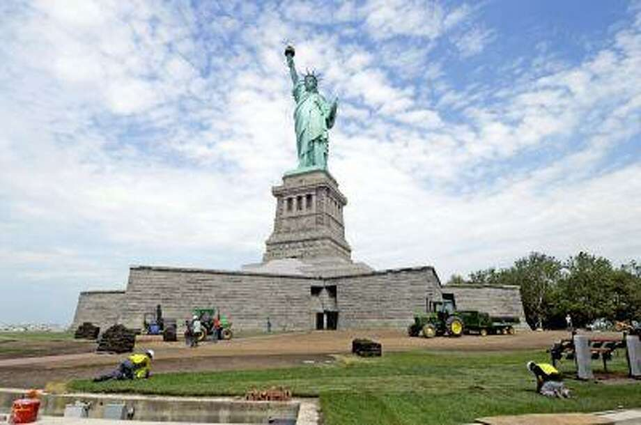 In this June 26, 2013 photo provided by the National Park Service, workers on Liberty Island install sod around the national monument which is set to re-open on the 4th of July, in New York. Months after railings broke, docks and paving stones were torn up and buildings were flooded by Superstorm Sandy, the Statue of Liberty will finally welcome visitors again. (AP Photo/National Park Service) Photo: ASSOCIATED PRESS / AP2013