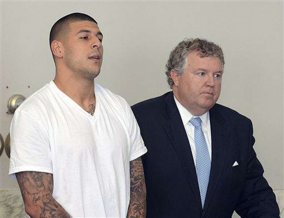 FILE - In this June 26, 2013, file photo, Aaron Hernandez, left, stands with his attorney, Michael Fee, right, during arraignment in Attleboro District Court in Attleboro, Mass. Since Hernandez was arrested last week in the shooting death of a friend whose body was found a mile away from his home, a portrait has emerged of a man whose life away from the field included frequent connections with police-related incidents that started as long ago as his freshman year at the University of Florida. (AP Photo/The Sun Chronicle, Mike George, Pool) Photo: AP / Pool The Sun Chronicle