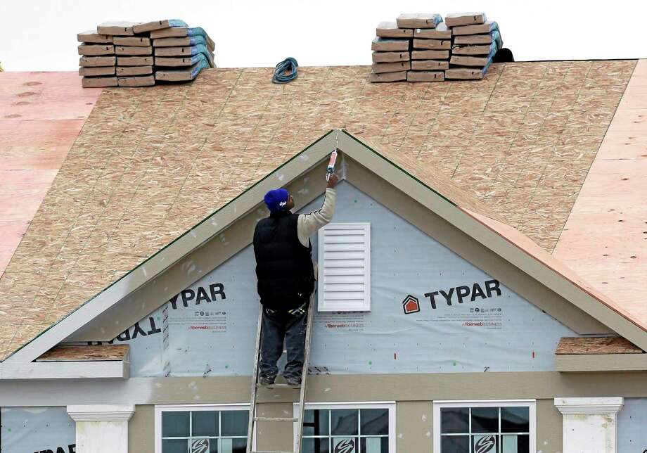 In this Monday, Nov. 11, 2013 photo, a worker caulks the peak of a new condominium complex under construction in Pepper Pike, Ohio. The Commerce Department releases new home sales for November on Tuesday, Dec. 24, 2013. (AP Photo/Tony Dejak) Photo: AP / AP