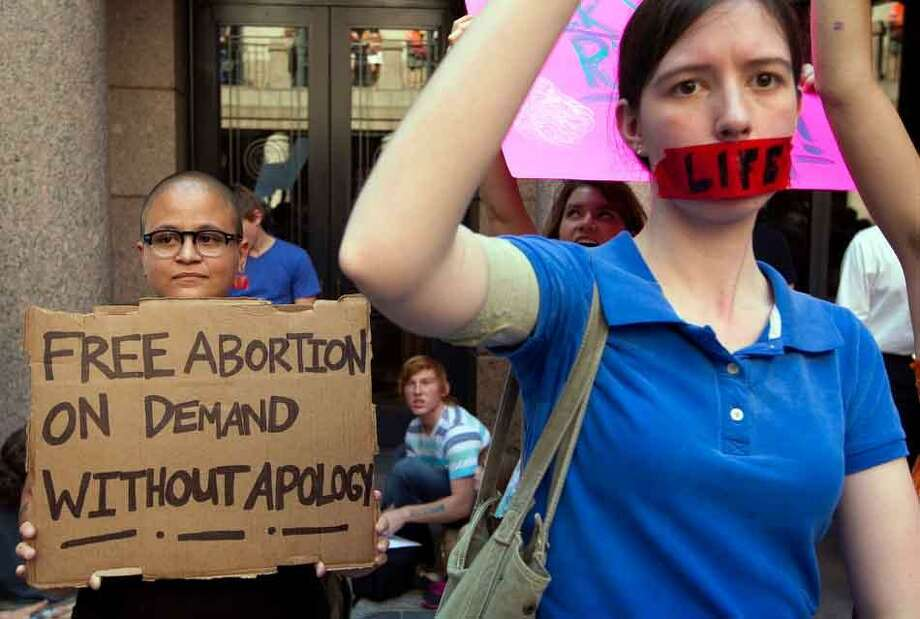 Pro-abortion rights supporter Yatzel Sabat, left, and anti-abortion protestor Amanda Reed demonstrate at the state Capitol in Austin, Texas, on Tuesday July 2, 2013.  Gov. Rick Perry has called lawmakers back for another special session with abortion on the top of the agenda. (AP Photo/Austin American-Statesman, Jay Janner) Photo: AP / Austin American-Statesman