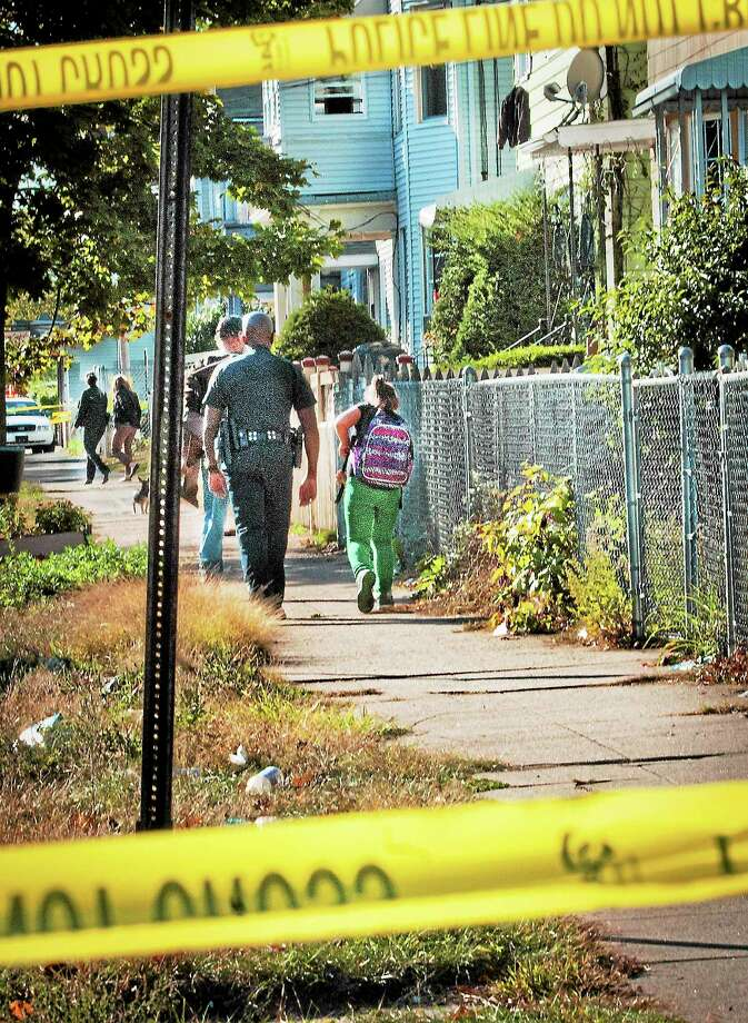 (Melanie Stengel — New Haven Register) A Police officer escorts a student home from school down Lombard Street.  Police have the are roped off due to a shooting.10/21. Photo: Journal Register Co.