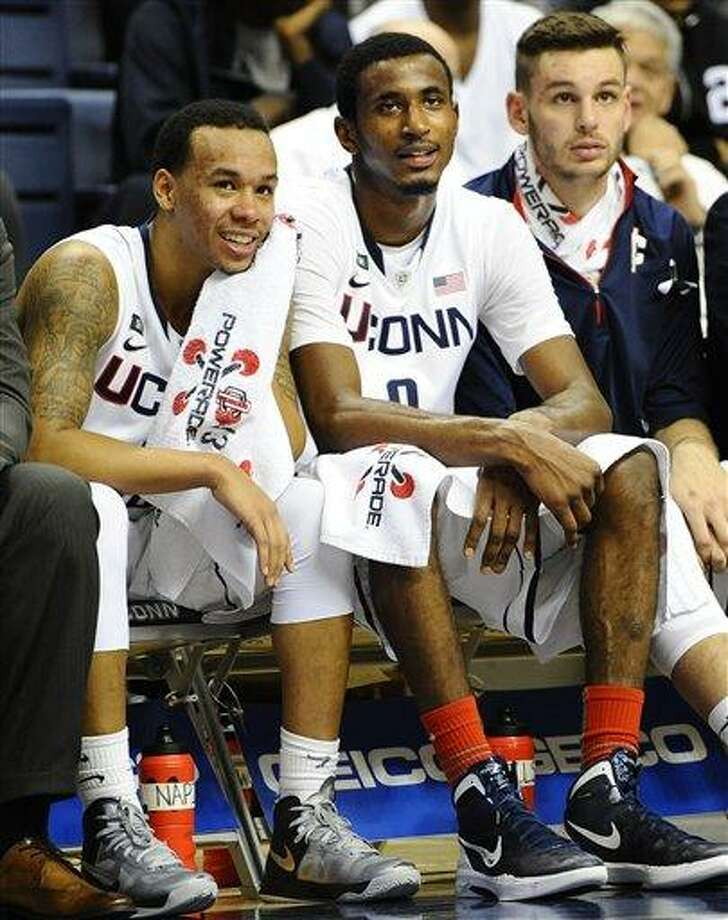Connecticut's Shabazz Napier, DeAndre Daniels, and Enosch Wolf, right, watch the final minutes of play in an NCAA college basketball game against DePaul in Storrs, Conn., Tuesday, Jan. 8, 2013. Connecticut won 99-78. (AP Photo/Jessica Hill) Photo: ASSOCIATED PRESS / A2013