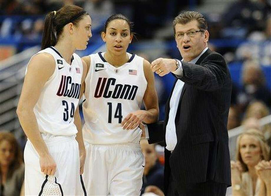 Connecticut head coach Geno Auriemma, right, talks with Connecticut's Kelly Faris and Bria Hartley in the first half of an NCAA college basketball game in the semifinals of the Big East Conference women's tournament in Hartford, Conn., Monday, March 11, 2013. (AP Photo/Jessica Hill) Photo: AP / FR125654 AP