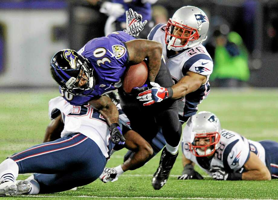 Baltimore Ravens running back Bernard Pierce (30) is tackled by New England Patriots free safety Devin McCourty, left, and New England Patriots cornerback Logan Ryan in Sunday's game. Photo: Nick Wass  — The Associated Press   / FR67404 AP