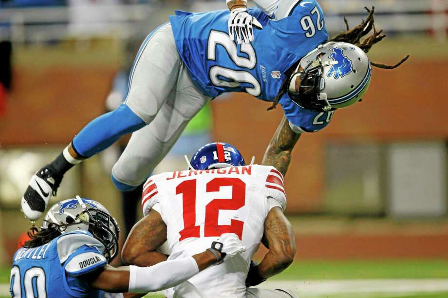 Detroit Lions free safety Louis Delmas (26) flies over New York Giants wide receiver Jerrel Jernigan (12) as Jernigan catches a touchdown pass defended by cornerback Bill Bentley (28). Photo: Paul Sancya — The Associated Press   / AP