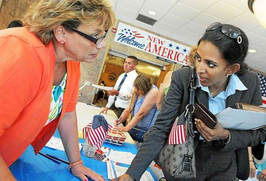 Catherine Avalone - The Middletown Press Republican Registrar of Voters Janice A. Gionfriddo registers Stamford resident Lakshmi Dharmarajan, at right, of India to vote after becoming a U.S. citizen at the Naturalization Ceremony Wednesday afternoon in the council chambers at City Hall in Middletown. / TheMiddletownPress