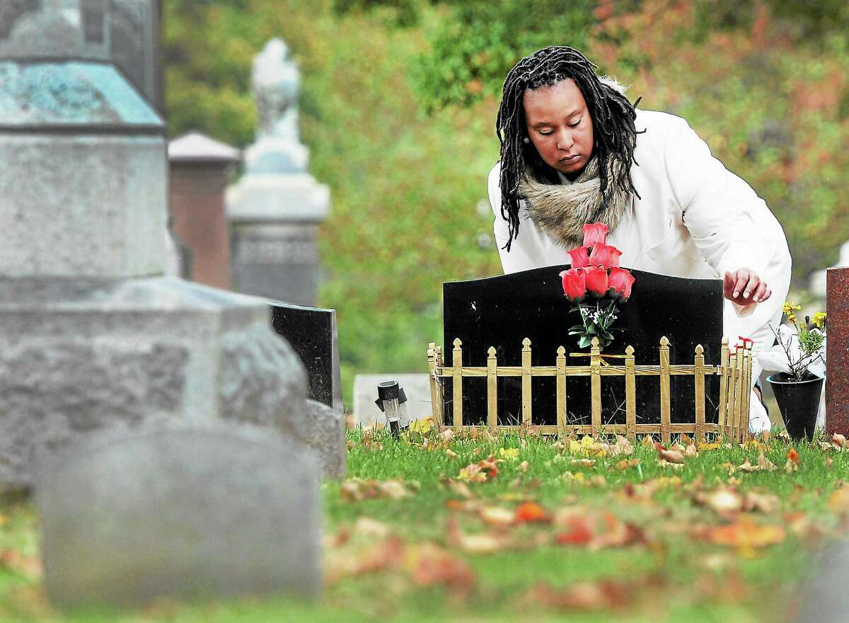 Lauren Pittman, 29, at the Evergreen Cemetery in New Haven, 2013 by the grave of her brother, Christopher Fain, 19, who was gunned down in the city.