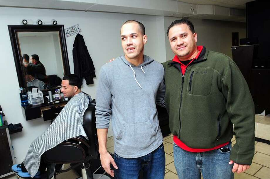 Barbers Luis Rivera, center, and Michael Cuevas, right, are photographed Thursday at Xplicit Hair Studio on 314 Grand Ave. in New Haven. The barbers are credited with noticing Jacob Wilson, 10, in front of the barber shop Thursday morning and bringing him into the shop and then alerting police. Wilson had been missing since the previous day. Arnold Gold/New Haven Register