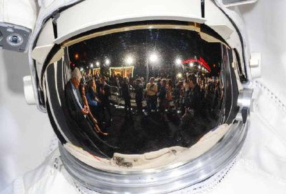 "The ""Gravity"" premiere red carpet as seen from a reflection in an astronaut's helmet at the AMC Lincoln Square Theaters on Tuesday, Oct. 1, 2013, in New York."
