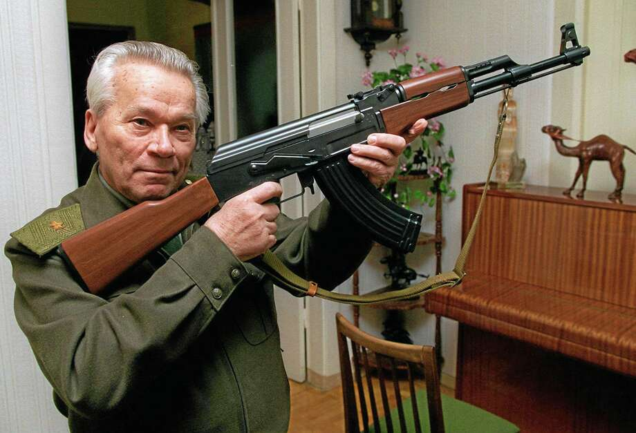 FILE- In this Wednesday, Oct. 29, 1997 file photo Mikhail Kalashnikov shows a model of his world-famous AK-47 assault rifle at home in the Ural Mountain city of Izhevsk, 1000 km (625 miles) east of Moscow, Russia. Kalashnikov, whose work as a weapons designer for the Soviet Union is immortalized in the name of the worldís most popular firearm, died Monday at the age of 94 in a hospital of the city of Izhevsk where he lived. The AK-47 has been favored by guerrillas, terrorists and the soldiers of many armies. An estimated 100 million guns are spread worldwide.  (AP Photo/Vladimir Vyatkin, File) Photo: AP / AP