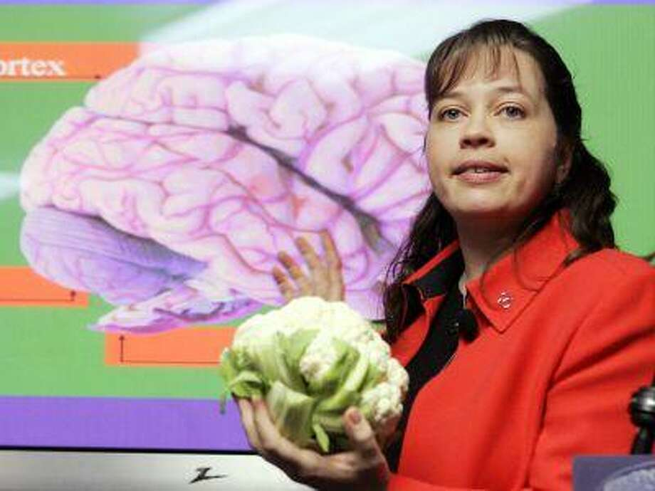 Elizabeth Edgerly, Ph. D., area program director for the Alzheimer's Association's Northern California/Northern Nevada Chapter, holds a head of cauliflower, comparing it to the size and weight of a human brain during a press briefing at the International Conference on Prevention of Dementia. (AP Photo/Manuel Balce Ceneta) Photo: ASSOCIATED PRESS / AP