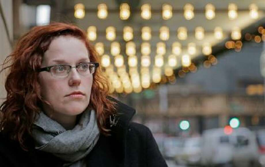 In this Dec. 3, 2013 photo, actor Adrienne Matzen poses in Chicago's theater district. Matzen, 29, who has been mostly uninsured since she turned 21, is now looking for a low monthly premium insurance plan on the federal website.
