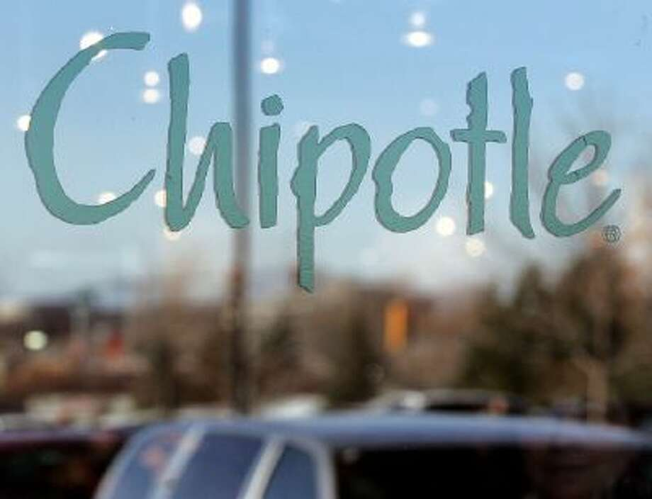 A patron's face, bottom right, is slightly visible beyond signage through a window of a Chipotle restaurant December 2, 2005 in Glenview, Illinois.