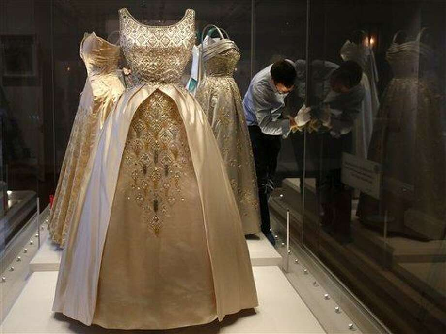 In this photo taken Monday, July 1, 2013, an employee cleans the glass cabinet displaying dresses worn by Queen Elizabeth II at the Fashion Rules exhibition at Kensington Palace in London. Opening on 4 July, a new glamorous exhibit at Kensington Palace showcases how the styles of three royal ladies; Queen Elizabeth II, her sometimes risque sister Margaret, and the glamorous Princess Diana, each reflected and influenced the trends of their fashion heyday. (AP Photo/Frank Augstein) Photo: AP / AP