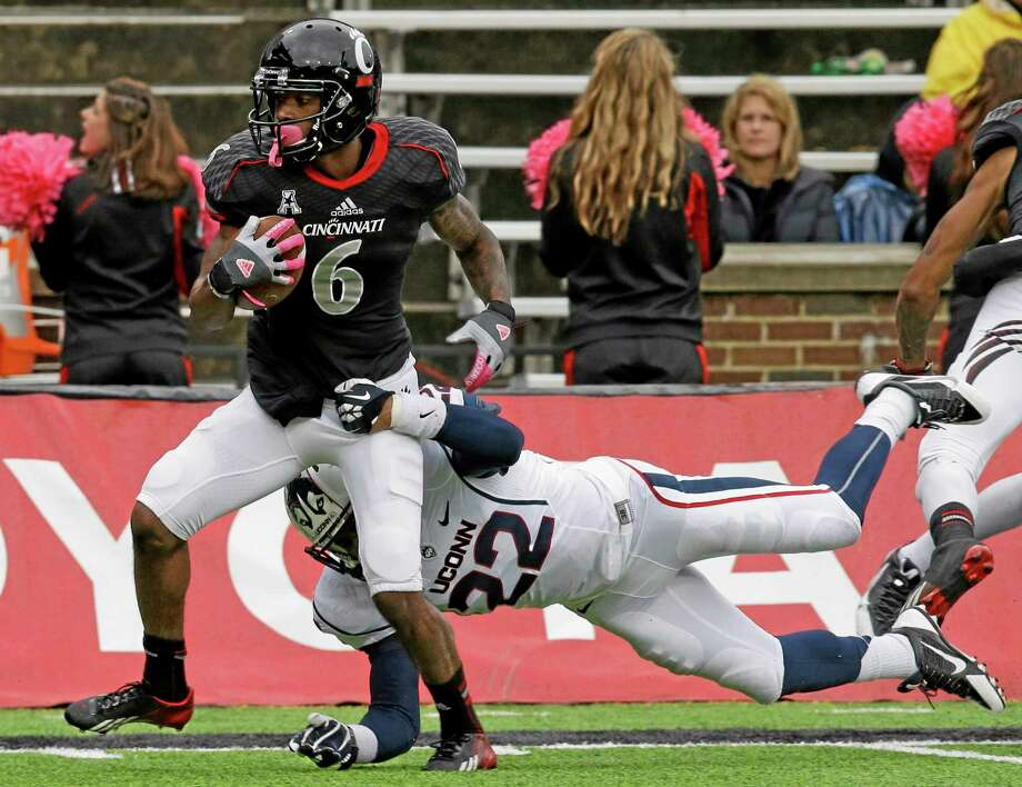 Cincinnati wide receiver Anthony McClung runs past UConn safety Andrew Adams for a 28-yard touchdown reception in the second half of the Bearcats' 41-16 win over the Huskies on Saturday in Cincinnati. Photo: Al Behrman — The Associated Press   / AP