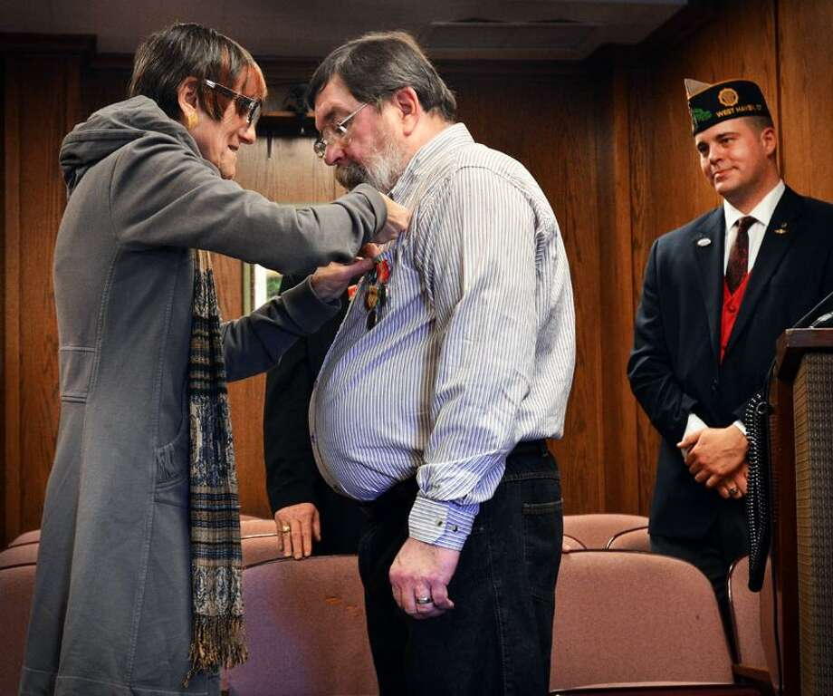 WEST HAVEN U.S. Rep. Rosa DeLauro (L) pins overdue medals on Viet Nam Veteran Michael Healey during a ceremony at Citry Hall.   Melanie Stengel/Register
