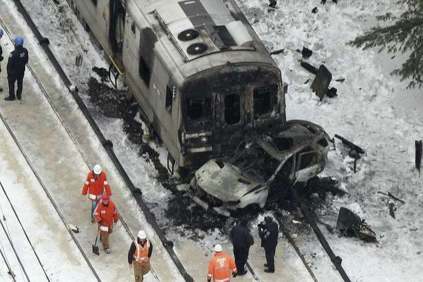 In this Feb. 4, 2015 photo, workers survey the scene of a deadly commuter train accident in Valhalla, N.Y., in which a packed Metro-North Railroad train slammed into a SUV stuck on the tracks and erupted into flames.