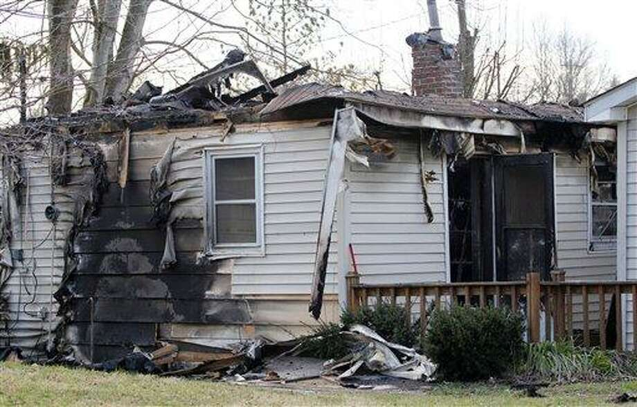 This Sunday, March 10, 2013 photo shows the charred remains of a home after a fire erupted, Saturday, March 9, 2013 in Gray, Ky, killing two adults and five children inside. (AP Photo/Lisa Norman-Hudson) Photo: AP / FR155776 AP