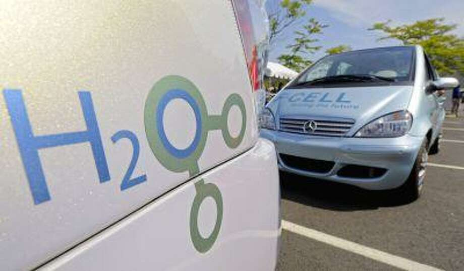 The logo on a hydrogen-powered GM vehicle, left, preceeds a hydrogen-powered Daimler vehicle on display at the Liberty Science Center in Jersey City, N.J., Wednesday Aug. 13, 2008. The cars are part of the 31-city, 2008 Hydrogen Road Tour that includes hydrogen powered vehicles from GM, Honda, Hyundai-Kia, Nissan, Toyota, and Volkswagen. (AP Photo/Richard Drew) Photo: ASSOCIATED PRESS / AP2008