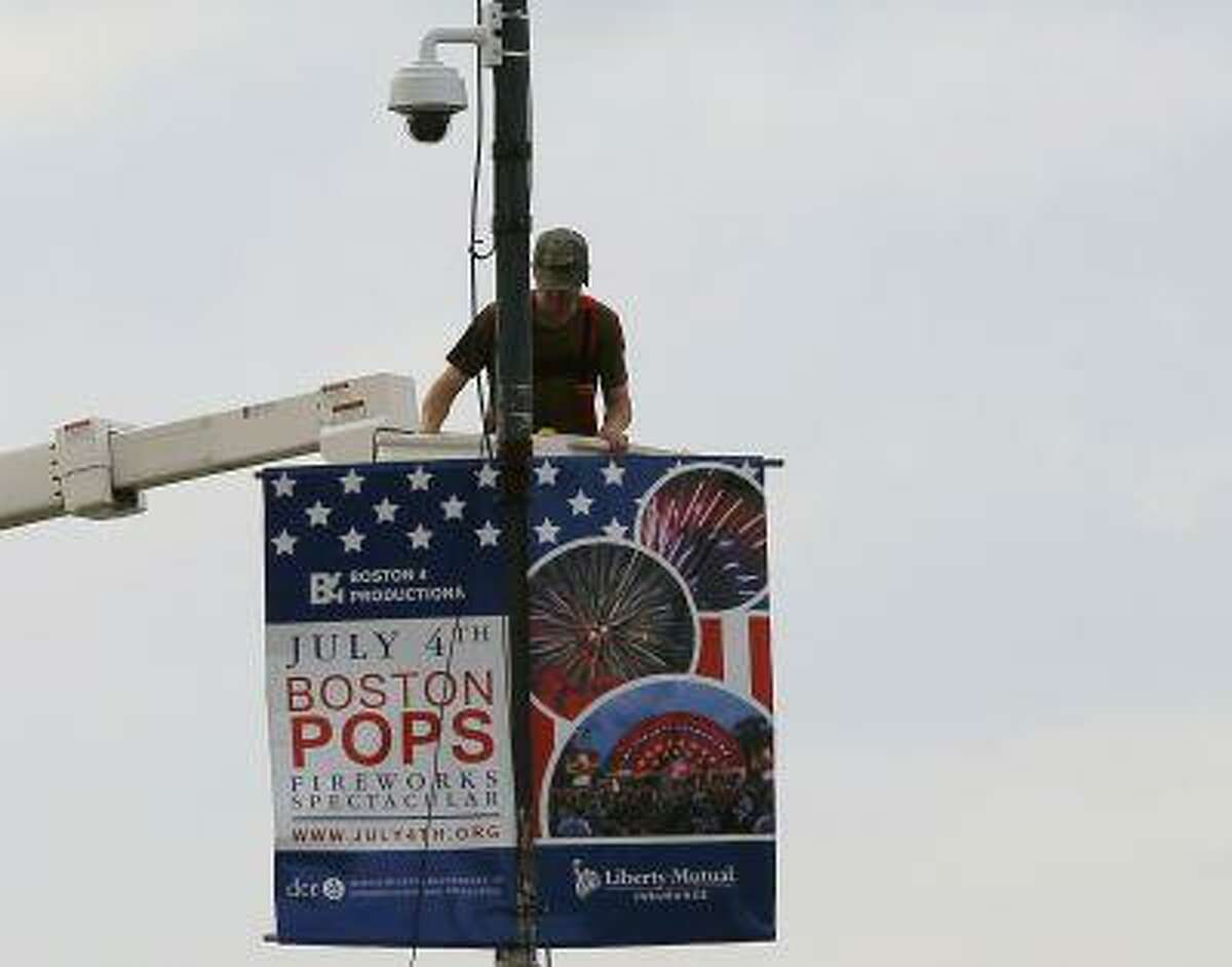 A worker installs a piece of security equipment on a lamp post on a bridge over the Charles River in Boston, Massachusetts July 2, 2013, in preparations for the city's Fourth of July celebrations. (Brian Snyder/Reuters)