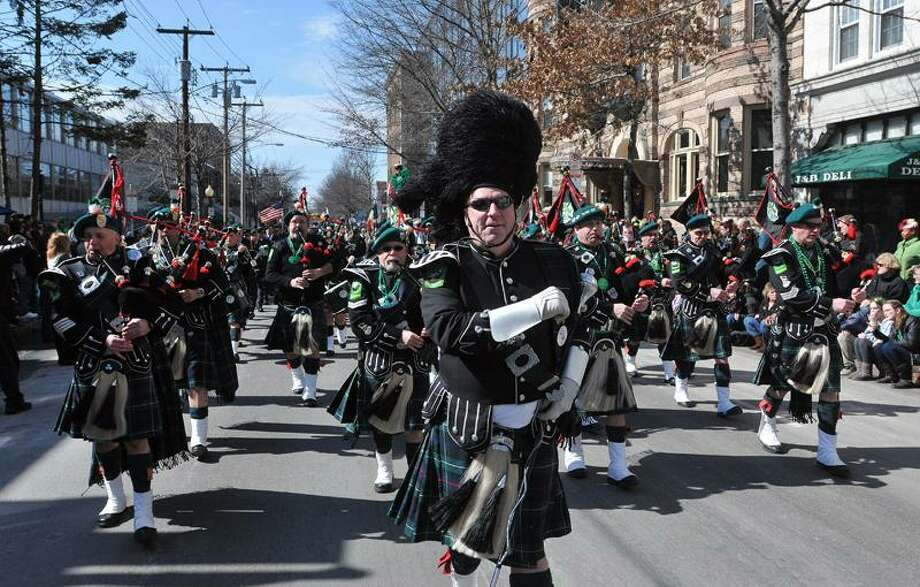 Retired firefighter John Hines leads the New Haven County Firefighters Emerald Society Pipe and Drum band along Chapel Street during the St. Patricks Parade.   Photo/Peter Casolino