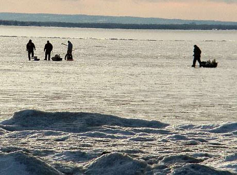 Ice fishermen are silhouetted on Oneida Lake as they fish on Thursday off of Lakeshore  Road in North Bay. There is 5 to 8 inches of ice where they are fishing.