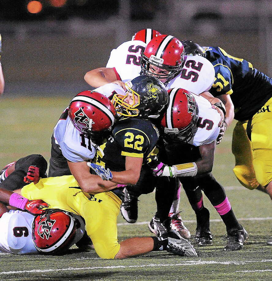 (Peter Casolino — New Haven Register)  East Haven's Nick Poulin gets wrapped up by the Wilbur Cross defense during the first quarter. Photo: Journal Register Co.