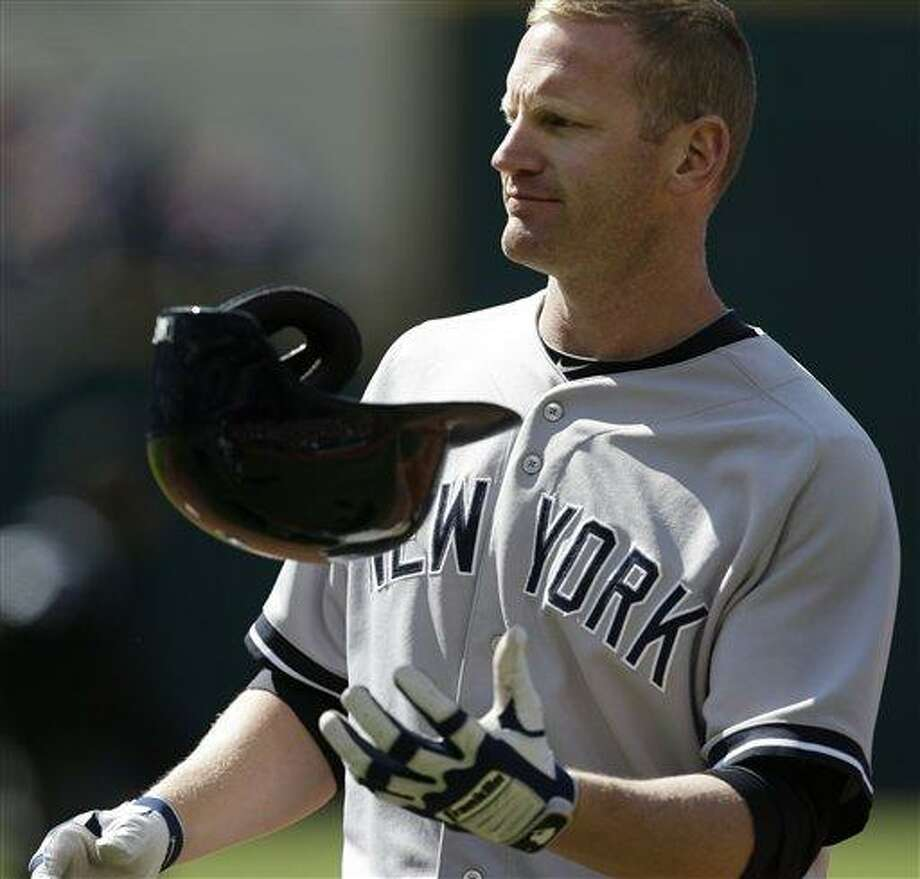 New York Yankees' Lyle Overbay tosses his helmet after flying out to left field in the third inning in the second baseball game of a doubleheader against the Cleveland Indians, Monday, May 13, 2013, in Cleveland. (AP Photo/Tony Dejak) Photo: AP / AP