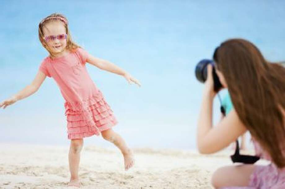 Mother photographing her daughter.