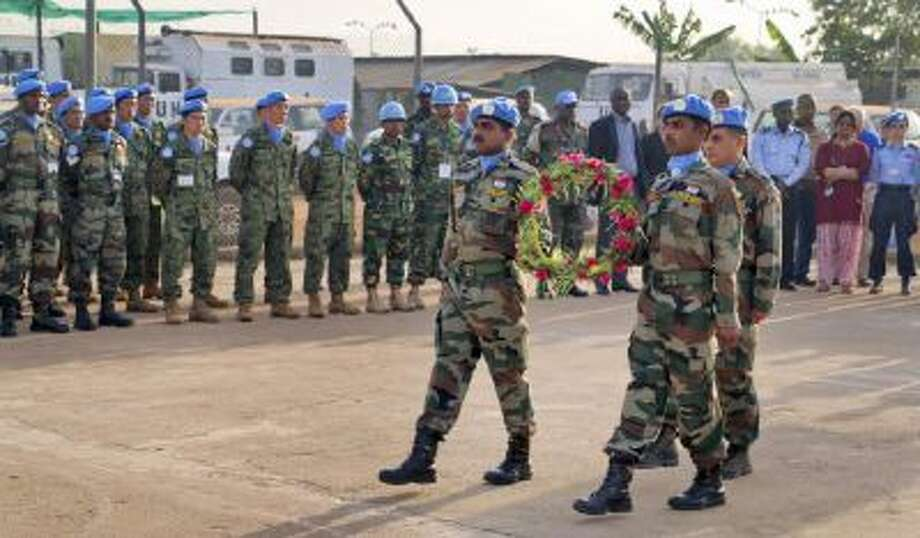 In this photo released by the United Nations Mission in South Sudan (UNMISS), U.N. peacekeepers walk to lay flowers on coffins of their two colleagues who were killed on Thursday, at a memorial service held in the UNMISS compound in Juba, South Sudan, Saturday, Dec. 21, 2013.