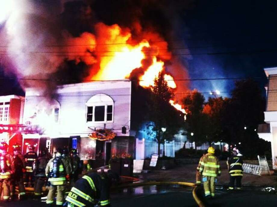 Coby Serfass Special to the Register  Firefighters fight   an early morning fire destroyed the building that contains the Village Pizza and Madison Wine Shop June 20, 2013.