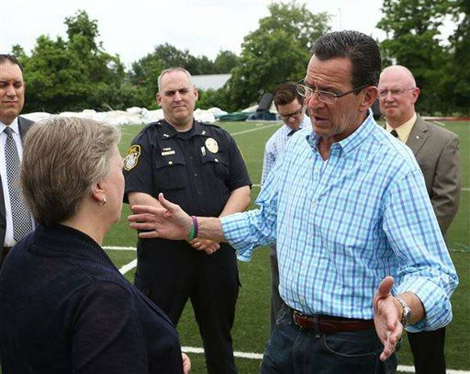 East Windsor First Selectman Denise Menard, left, speaks with Connecticut Governor Dannel Malloy, right, at Sports World in East Windsor, Conn. on Tuesday, July 2, 2013. Gov. Malloy was touring the damage caused by Monday's tornado. Twenty-nine campers were in the domed bubble on Monday, but were safely clear of it and undercover before the tornado hit. The twister which formed in Windsor Conn. and spread a 2 1/2 mile long path of damage generated winds up to 86 miles per hour. (AP Photo/Journal Inquirer, Jared Ramsdell) Photo: AP / Journal Inquirer
