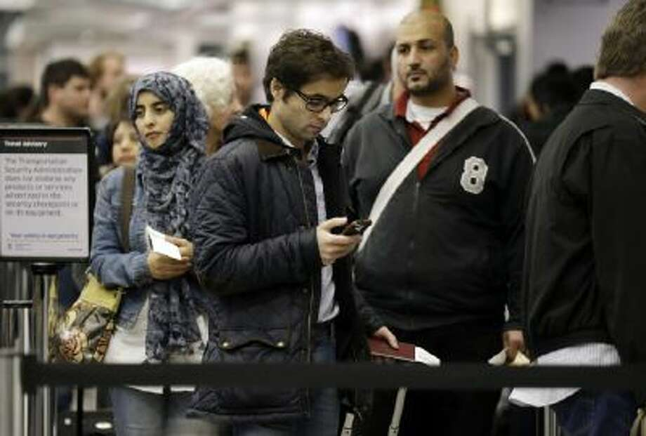 Passengers wait in the security line at Terminal 3 at O'Hare International Airport in Chicago on Friday, Dec. 20, 2013.