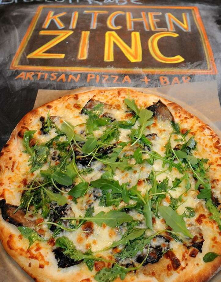The porotobello pizza with portobello mushrooms, balsamic marinade, caramelized onions, Fontina cheese, topped with arugula salad at Kitchen Zinc.  Mara Lavitt/New Haven Register12/06/12
