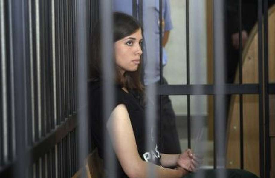 In this Friday, July 26, 2013 photo, Nadezhda Tolokonnikova (foreground right) a member of the feminist punk band Pussy Riot, listens from behind bars at a courtroom at a district court in Saransk.