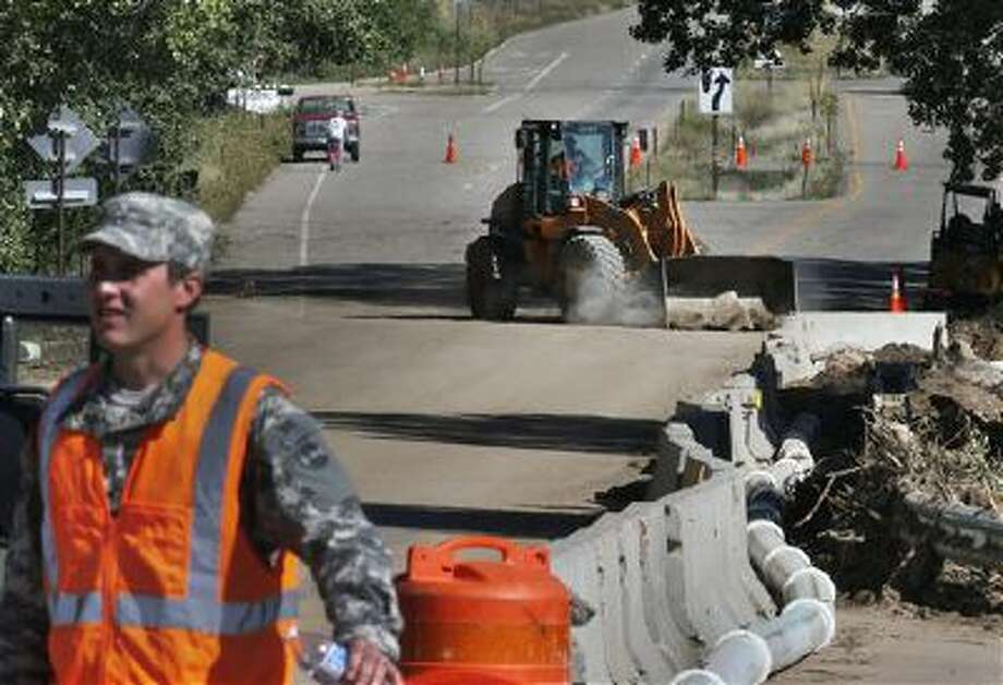 A Colorado National Guard soldier mans a roadblock Sept. 20 as a bulldozer works on a damaged road being repaired after Colorado's recent floods. The federal government shutdown had hampered highway repair funding, but that looks to be resumed. Photo: AP / AP
