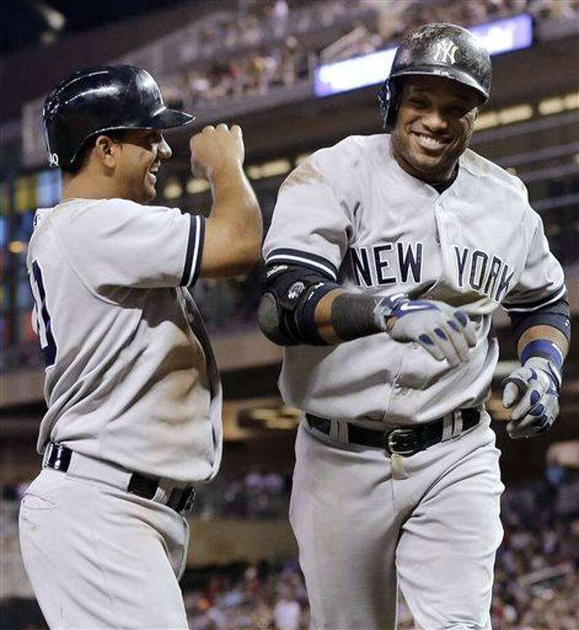 New York Yankees' Alberto Gonzalez, left, and Robinson Cano celebrate Cano's seventh-inning, three-run home run off Minnesota Twins pitcher Anthony Swarzak in a baseball game Tuesday, July 2, 2013 in Minneapolis. Gonzalez had three RBIs for the Yankees. who won 7-3. (AP Photo/Jim Mone) Photo: AP / AP