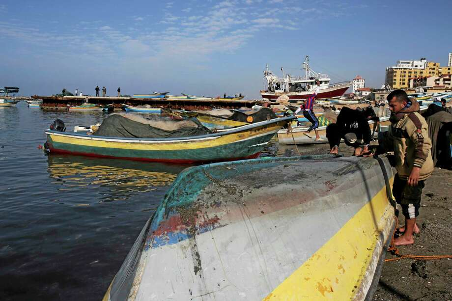 Palestinian fishermen fix and clean their boat before sailing into the Mediterranean Sea at the fishermen's port in Gaza City Dec. 17. Photo: Adel Hana — The Associated Press   / AP