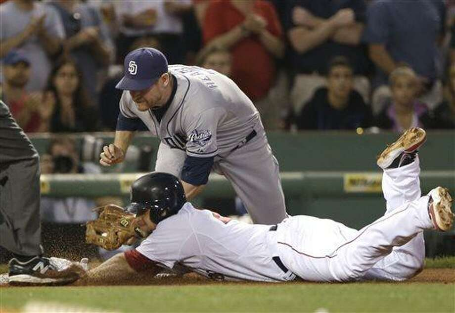San Diego Padres third baseman Chase Headley puts the tag on Boston Red Sox's  Brandon Snyder who is out trying to stretch a double into a triple during the fourth inning of an interleague baseball game at Fenway Park in Boston, Tuesday, July 2, 2013. Three runs scored on Snyder's double. (AP Photo/Elise Amendola) Photo: AP / AP